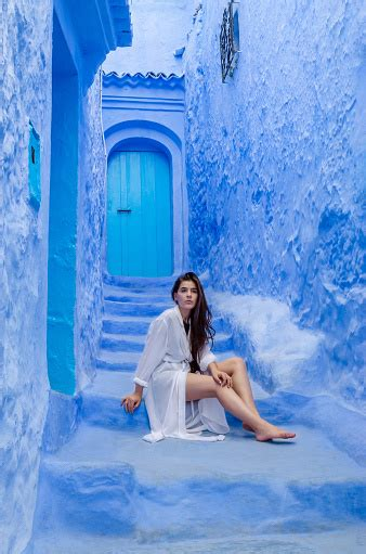 Beautiful Girl In A White Dress Against A Blue City